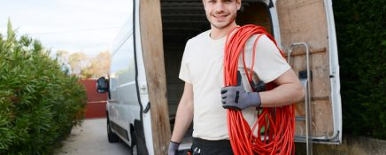 handsome young construction worker with his commercial van on background