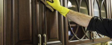 A man cleaning a wooden kitchen cabinet.