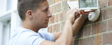 Security Consultant Fitting Security Light To House Wall