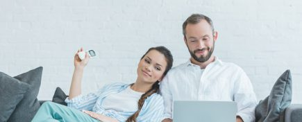 couple turning on air conditioner during the summer heat while using laptop